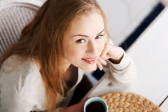 Beautiful caucasian woman sitting by a table with black coffee. Stock Photos