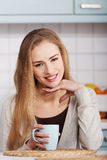 Beautiful caucasian woman is sitting by table with cup of coffee Stock Photography