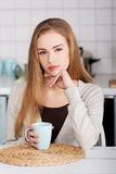 Beautiful caucasian woman is sitting by table with cup of coffee Royalty Free Stock Photos