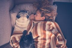 Beautiful caucasian woman sleep at home in winter with two best friends dog pugs together lay down with love. protection and royalty free stock photos