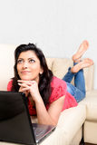 Beautiful Caucasian woman smiles, thinking lying on the couch Stock Photo