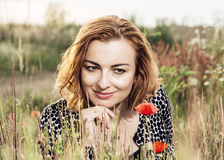 Beautiful caucasian woman is smiling and posing in poppy flowers Stock Photography