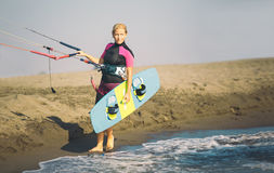 Beautiful Caucasian woman sufrer holding control bar and kiteboard. And standing by the sea Royalty Free Stock Image