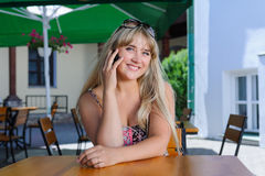 Beautiful caucasian woman talking on the phone at a cafe. Young pretty blonde woman at a cafe outside on street smiling happy talking on phone, lifestyle people Stock Photography