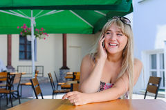 Beautiful caucasian woman talking on the phone at a cafe. Young pretty blonde woman at a cafe outside on street smiling happy talking on phone, lifestyle people Royalty Free Stock Photo