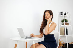 Beautiful Caucasian woman talking on the phone while using laptop on white desk over clean home office with copy space Royalty Free Stock Photo