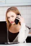 Beautiful caucasian woman talking through phone and working with Royalty Free Stock Image