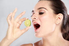 Beautiful caucasian woman trying to eat a slice of lime Royalty Free Stock Images