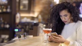 Beautiful caucasian woman uses phone and relaxes in cafe sitting on counter bar. Beautiful young woman sits next to the counter bar in the pub and messaging with stock video