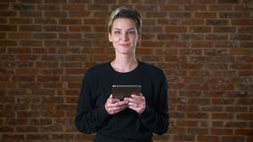 Beautiful caucasian woman is using her tablet and smiling charming at camera on brick background isolated.  stock video
