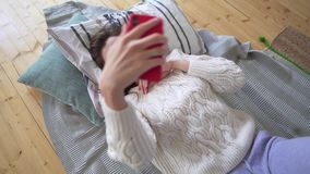 Beautiful caucasian woman in a white knitted sweater takes a selfie while lying on a cozy plaid and pillow in her. Bedroom 4k stock footage