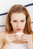 Beautiful caucasian woman in white lingerie is drinking small co Royalty Free Stock Photos
