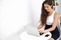 Beautiful Caucasian woman working on laptop on white desk over white  background with copy space Royalty Free Stock Images