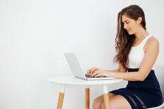 Beautiful Caucasian woman working on laptop on white desk over white isolated background with copy space Royalty Free Stock Images