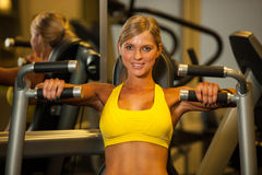 Beautiful caucasian woman working out her arms in fitness. Beautiful caucasian woman working out in fitness Royalty Free Stock Image