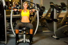 Beautiful caucasian woman working out her arms in fitness Royalty Free Stock Images
