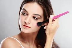Beautiful caucasian women applying blush Royalty Free Stock Images