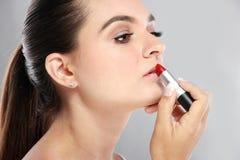 Beautiful caucasian women applying lipstick Royalty Free Stock Photo