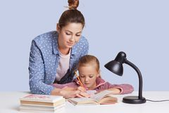 Beautiful Caucasian woman helping her doughter to do school homework, mother and child surronded by books, little girl sitting stock images