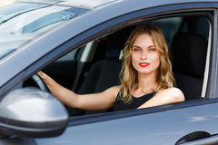 Beautiful caucasian young blond woman sitting behind wheel of car Stock Images