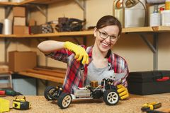 Beautiful caucasian young woman working in carpentry workshop at table place royalty free stock photo