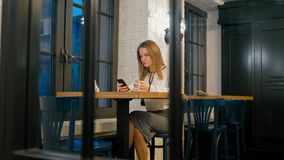 Business Woman is Using Smartphone App and Drinking Coffee in Cafe at Night stock video footage