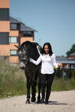 Beautiful caucasian young woman and horse walking Royalty Free Stock Image