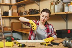 Beautiful caucasian young woman working in carpentry workshop at table place royalty free stock images