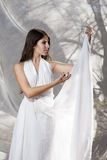 Beautiful caucasian young woman in white dress. Beautiful caucasian young woman posing in white dress outdoor royalty free stock photos
