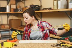 Beautiful caucasian young woman working in carpentry workshop at table place. Beautiful caucasian young brown-hair woman in plaid shirt, gray T-shirt, yellow royalty free stock images