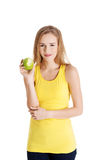 Beautiful causal caucasian woman holding fresh green apple with Stock Photography