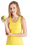 Beautiful causal caucasian woman holding fresh green apple with Royalty Free Stock Photos