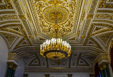 Beautiful ceiling in the Hermitage. The rich interior of the Hermitage Museum in St. Petersburg. Ceiling with gold, beautiful patterns and a large chandelier royalty free stock photo