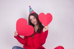 Beautiful celebrate girl with paper hearts and cap. Isolated on white Stock Photo