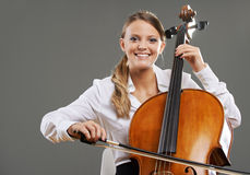 Beautiful cellist. Smiling young woman cellist on grey background royalty free stock photos