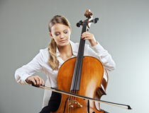 Beautiful cellist. Beautiful young woman cellist on grey background royalty free stock photos