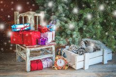 Beautiful chair, with Christmas presents under the tree. Watch and box with cones. Snowfall. The horizontal frame royalty free stock images