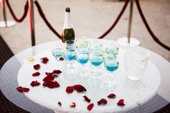 Beautiful champagne glasses on a glass table and petals of red r Stock Image