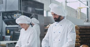 Beautiful charismatic three bakers working all together in a bakery industry forming pieces of dough for baking bread. Young baker man looking straight to the stock footage