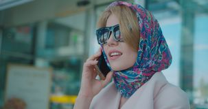 Beautiful charming blonde lady in sunglasses and scarf on her head is smiling while talking via the mobile phone near. The airport. 4k footage stock video footage