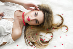 Beautiful charming blonde with long hair lying on the bed in a white bedroom. A gentle Sensual look. woman in bedroom Royalty Free Stock Photography