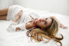 Beautiful charming blonde with long hair lying on the bed in a white bedroom. A gentle Sensual look. woman in bedroom Stock Images
