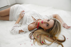 Beautiful charming blonde with long hair lying on the bed in a white bedroom. A gentle Sensual look. woman in bedroom Stock Image