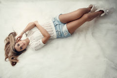 Beautiful charming blonde with long hair lying on the bed in a white bedroom. A gentle Sensual look. woman in bedroom Royalty Free Stock Images