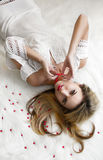 Beautiful charming blonde with long hair lying on the bed in a white bedroom. A gentle Sensual look. woman in bedroom Royalty Free Stock Image