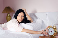 Beautiful charming dreamy young woman lying in bed turns off alarm clock on the bedside table Stock Photo