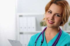 Beautiful charming friendly smiling female medicine therapeutist. Doctor standing in office, holding document pad and looking in camera. Medical help, physician Royalty Free Stock Images