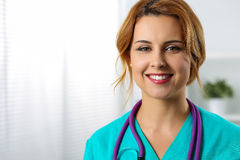 Beautiful charming friendly smiling female medicine therapeutist. Doctor standing in office and looking in camera. Medical help, physician reception or Stock Images