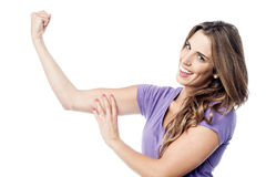 Beautiful charming girl flexing her biceps Royalty Free Stock Photo