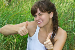 Beautiful charming girl shows the thumbs up. Beautiful young and charming girl with bare shoulders in a white t-shirt smiles and shows the thumbs up Stock Image